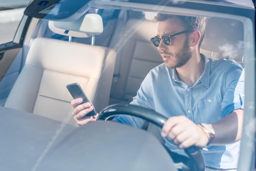 мужчина в машине со смартфоном